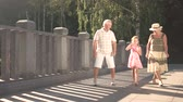 family values : Child with bubble blower and grandparents. Couple of senior people walking with their granddaughter outdoors, girl blowing soap bubbles. Beautiful family leisure. Stock Footage