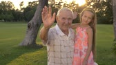 unoka : Grandfather and girl waving with hands. People showing greeting gesture. Happy family relationship.