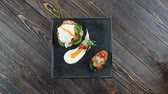 espinafre : Garnished eggs benedict. Tasty food, brown wooden background. Stock Footage