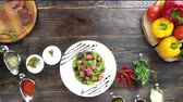 beef dish : Hand of chef garnishing salad. Food on brown wooden table. Stock Footage