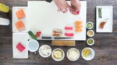 seafood recipe : Hands of chef making sushi. Japanese food, wooden table.