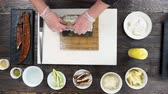 унаги : Unagi sushi roll preparation. Hands making food, wooden table.