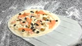 mediterranean mussel : Uncooked pizza on a shovel. Shrimps, salmon and olives.