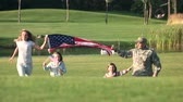 quatro pessoas : Patriotic family running with huge USA background outdoor. Soldier father. Lake in the park background.