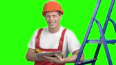 bonfile : Cheerful engineer with pc tablet. Worker in yellow helmet with pc tablet working with a project, chroma key background.