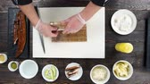 унаги : Hands shaping a sushi roll. Japanese food preparation, wooden table. Стоковые видеозаписи