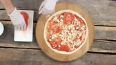 моцарелла : Hands making pizza, wooden table. Crust, cheese and fresh tomato. Стоковые видеозаписи