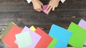 workspace : Hands making origami, top view. Male hands folding paper sheet on wooden background. Origami workshop concept. Stock Footage