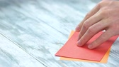 workspace : Man creating origami close up. Male hands dividing paper sheet in half. Paper folding lesson.
