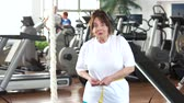 centymetr : Senior woman measuring her waist at gym. Elderly woman expressing success after measuring herself with tape at fitness club. Weight loss after sport training. Wideo