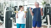 uzun ömürlü : Elderly couple working out at gym. Happy senior man and woman lifting dumbbells at gym. Beautiful elderly people at fitness club.
