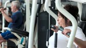 uzun ömürlü : Female pensioner training at gym, side view. Attractive senior woman working out at fitness center close up. Sport, wellness and healthcare.
