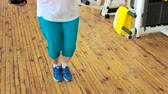 uzun ömürlü : Woman jumping with rope on wooden floor. Woman in blue sneakers jumping with skipping rope indoor. Sport and healthy lifestyle. Stok Video