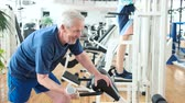 uzun ömürlü : Elderly man lifting dumbbell at modern gym. Smiling senior man working out with weight at fitness center. Retirement and sport. Stok Video