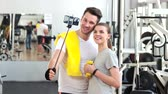 törülköző : Smiling couple talking a selfie at gym. Young man and woman in sportswear taking selfie with monopod at fitness club. Woman holding dumbbell.