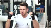 trener : Handsome guy in white shirt training at gym. Fit young man is doing chest workout on the machine in gym. Perfect body through efforts.