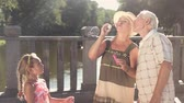 dede : Child and her grandparents outdoors. Cute couple of senior people with bubble blower on bridge, slow motion. Granddaughter and her grandparents spending good time together.