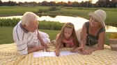 unoka : Grandparents helping granddaughter to draw. Little girl and grandparents outdoors. Art skills development.