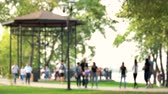 inserir : Blurred defocused people are walking in the park. Blur people walking in the city park at sunny summer day.