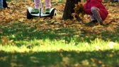 electric scooters : Riding on the grass covered with fallen leaves. Close up. Little girl picking up and gathering yellow oak leaves.
