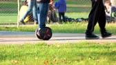 wheeled : Boy riding gyroscooter in the park. Walking strolling people. Autumn park. Stock Footage
