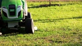 john : Ukraine, Kiev 17.09.2017. Green lawn mower tractor. Riding grass cutter motion, close up. Stock Footage
