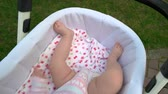 baby carriage : Newborn baby lying in carriage. Sweet bare legs on baby. Infant child outdoors.