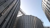 complicado : Stainless steel grain bins, up view. Gather of metal buildings.