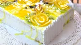 orange jelly : Chef decorating cake with white cream. Cake covered with fresh fruits slices and jelly. Delicious dessert for gourmet. Stock Footage