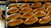bakery shop : Baked buns on oven tray. Manufacturing process of baking buns. Worker at pastry shop. Stock Footage