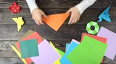 krok : Folding origami paper in triangle, top view. Man making origami figures. Colourful papers.