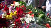 veterán : People folding flowers in memory of victims. Close up. Many bouquets of different flowers.