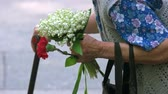 memórias : Old senior grandma with flowers during memorial day. Close up. Very old lady with stick, flowers and bag.
