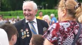 gratidão : 09.05.2018, Ukraine, Kiev. Old senior veteran talking with people outdoors. Victory day, may of 9. Crowded park.