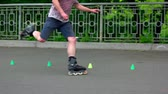 crossover : 09.05.2018, Ukraine, Kiev. Roller skater doing crossover tricks outdoors. Training agility markers. Unrecognizable man.