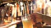pinta : Light beer pouring out of tap. Flowing down beer foam.