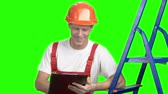 replacement : Male contractor writing on clipboard, green screen. Caucasian engineer worker making a note on black clipboard, alpha channel background.