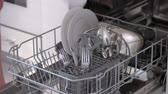 Close up woman taking out clean dishes from dishwasher. Unloading the dishwasher at home, fast motion.