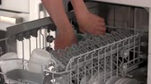 Hands take away clean glassware from dishwasher. Woman using modern dishwasher at home. Save your time with modern appliance.