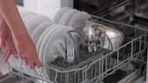Housewife taking out clean plates from dishwasher machine. Female hands unloading dishwasher close up. Modern appliance at home.