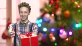 галстук бабочка : Boy with gift box on blurred Christmas background. Stylish teen boy giving red gift box and thumb up. Christmas holiday concept. Стоковые видеозаписи