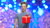 agradecimento : Boy giving present box to camera. Cheerful teen guy giving red gift box with bow and thumb up against blue bokeh background. Thanks for present.