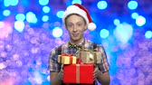 галстук бабочка : Christmas teen boy with gift boxes. Handsome teen guy in Santa Claus hat hoolding present boxes on blue bokeh background.