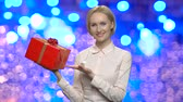 bluz : Woman with gift box on Christmas background. Cheerful business woman showing New Year gift box on blue bokeh background.