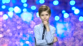 making a wish : Portrait of handsome child on blue bokeh background. Cute little boy with hand on chin. Kid making Christmas wish. Blue and purple shining lights background.