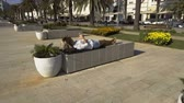 cellular : Woman lying on the bench on the promenade and browsing internet on cell phone Stock Footage