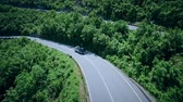 sarma : Aerial view of a curved winding road with cars passing. Mountain road