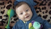 loutka : Portrait of a cute newborn with rattle looking at camera