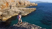 Young mother holds baby boy in her arms is standing on the edge of a cliff