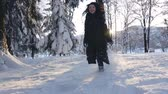Girl has fun runs between snowy trees in winter. Concept of happiness